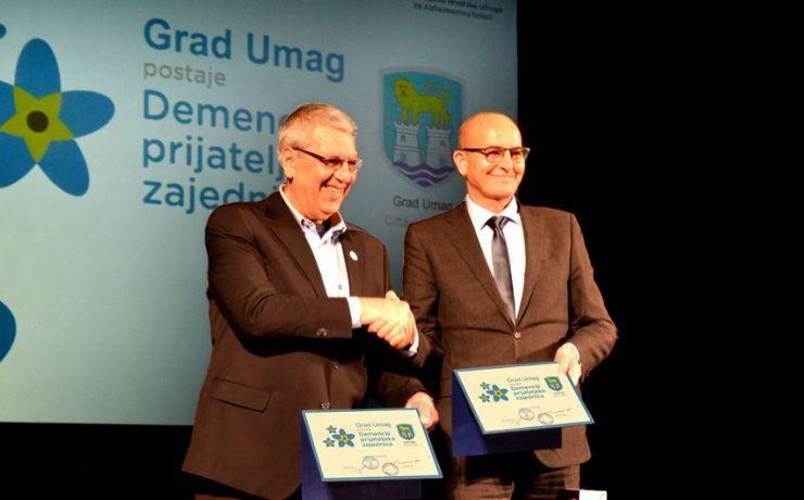 Tomislav Huić, voditelj inicijative Prijatelji demencije - Hrvatska (na slici lijevo) i Vili Basanesse, gradonačelnik Umaga, s poveljama o postajanju Grada Umaga Demenciji prijateljskom zajednicom.